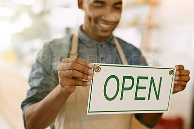 Buy stock photo Shot of a confident young man putting up a open sign on the door of his coffee shop to let customers know that they can come in