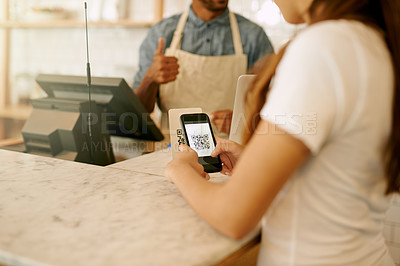 Buy stock photo Cropped shot of an unrecognizable young woman using her cellphone to pay her bill at a coffee shop during the day