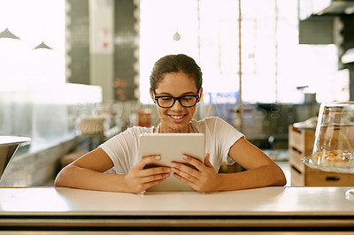 Buy stock photo Shot of a young woman using a digital tablet while working in a coffee shop