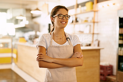 Buy stock photo Shot of a confident young woman standing with her arms folded inside of a coffe