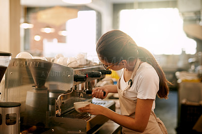 Buy stock photo Shot of a cheerful young woman making coffee inside of a cafe during the day