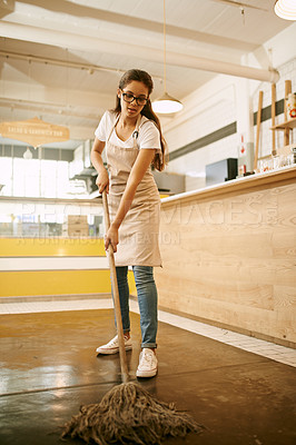 Buy stock photo Shot of a focussed young woman mopping the floor of a coffee shop during the day