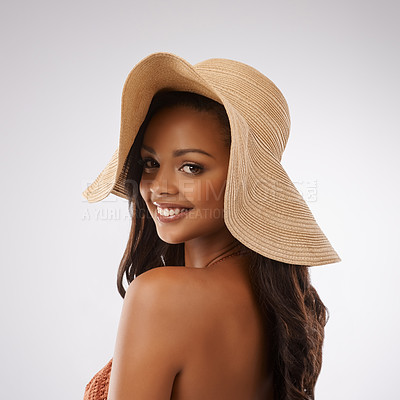 Buy stock photo Studio portrait of a beautiful young woman wearing a bikini and sunhat against a gray background