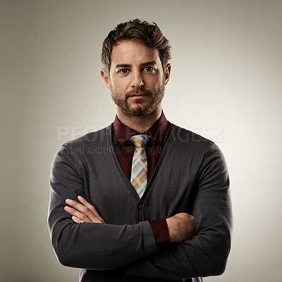 Buy stock photo Studio portrait of a handsome young businessman standing with his arms crossed against a grey background