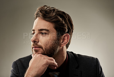 Buy stock photo Studio shot of a handsome young businessman looking thoughtful while sitting against a grey background