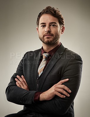Buy stock photo Studio portrait of a handsome young businessman sitting with his arms crossed against a grey background