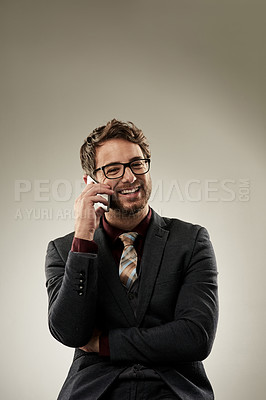 Buy stock photo Studio shot of a handsome young businessman making a call while standing a grey background