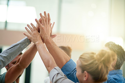 Buy stock photo Shot of a team of colleagues celebrating with a high five in a modern office