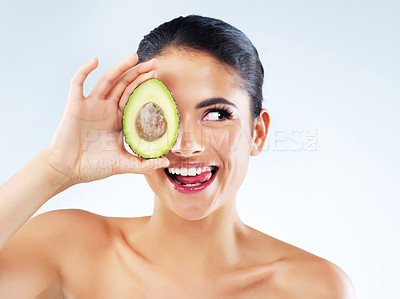 Buy stock photo Studio shot of an attractive young woman covering her eye with an avocado against a gray background