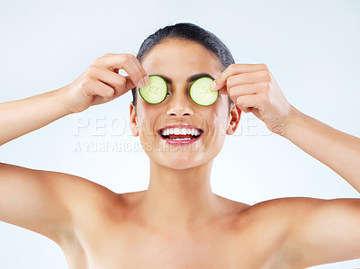 Buy stock photo Studio portrait of an attractive young woman covering her eyes with cucumbers against a gray background