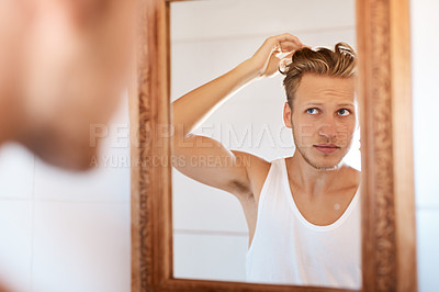 Buy stock photo Shot of a young man looking at his hair in the mirror at home