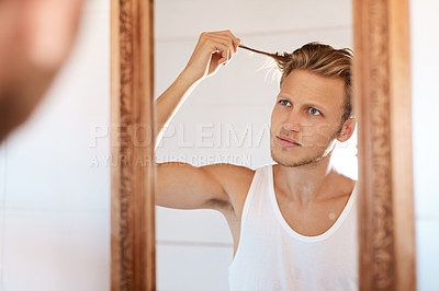 Buy stock photo Shot of a young man going through his morning routine