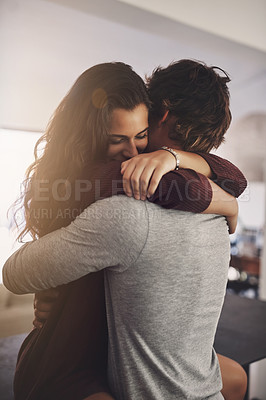 Buy stock photo Shot of an affectionate young couple hugging in the kitchen at home