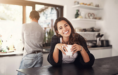 Buy stock photo Portrait of a young woman having coffee in the kitchen with her husband standing in the background