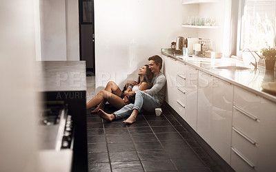 Buy stock photo Shot of an affectionate young couple sitting on the kitchen floor