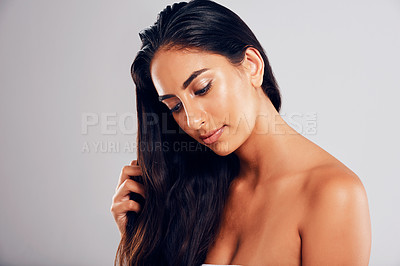 Buy stock photo Studio shot of a young beautiful woman posing against a gray background