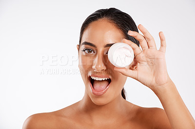 Buy stock photo Studio portrait of a beautiful young woman holding a container of lotion against a gray background