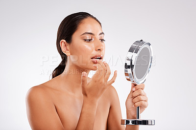 Buy stock photo Studio shot of a beautiful young woman examining her skin in a handheld mirror against a gray background