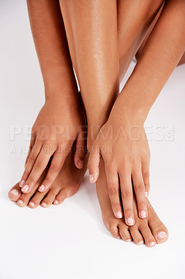 Buy stock photo Studio shot of an unrecognizable young woman's legs and hands against a gray background
