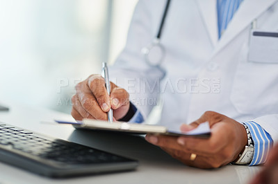 Buy stock photo Closeup shot of an unrecognizable doctor writing on a clipboard in his office