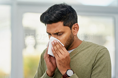 Buy stock photo Shot of a young man blowing his nose