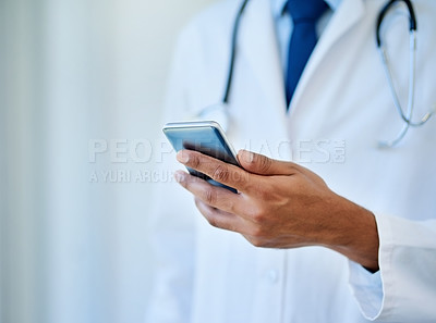 Buy stock photo Closeup shot of an unrecognizable doctor using a cellphone in a hospital