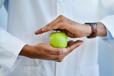 Buy stock photo Closeup shot of an unrecognizable doctor holding an apple in his hands