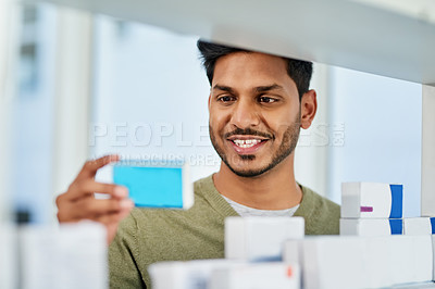 Buy stock photo Shot of a young man browsing through products in a pharmacy