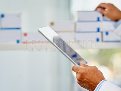Buy stock photo Closeup shot of an unrecognizable pharmacist working on a digital tablet in a chemist