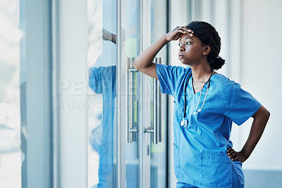 Buy stock photo Shot of a young female nurse looking stressed out while standing at a window in a hospital