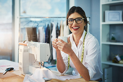 Buy stock photo Cropped portrait of an attractive young fashion designer enjoying a coffee while working in her design studio