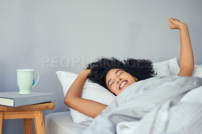 Buy stock photo Shot of a young woman waking up in bed in the morning and stretching
