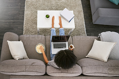 Buy stock photo High angle shot of a young woman using a laptop and having popcorn on the sofa at home