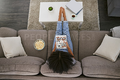 Buy stock photo High angle shot of a young woman using a digital tablet and having popcorn on the sofa at home