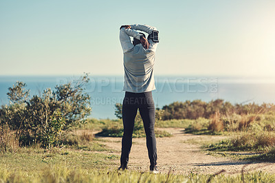 Buy stock photo Rearview shot of an unrecognizable young man stretching before exercising outdoors