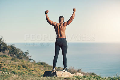 Buy stock photo Rearview shot of an unrecognizable young man standing with his hands raised while exercising outdoors