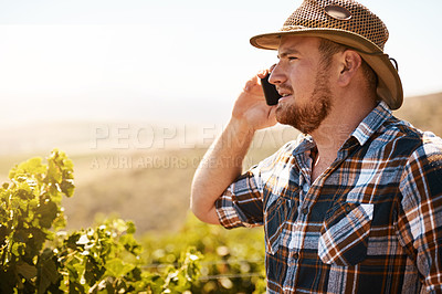 Buy stock photo Shot of a farmer talking on a cellphone in a vineyard
