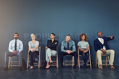 Buy stock photo Shot of a group of well dressed businesspeople seated in line while waiting to be interview