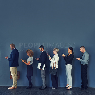 Buy stock photo Studio shot of a group of businesspeople using wireless devices while waiting in line