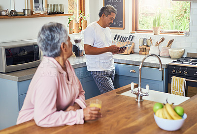 Buy stock photo Shot of an carefree elderly woman drinking orange jiuce in the kitchen while her husband is browsing on a digital tablet at home during the day