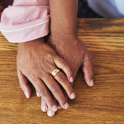 Buy stock photo High angle closeup of an unrecognizable couple holding hands on a table at home during the day