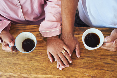 Buy stock photo High angle closeup of an unrecognizable couple holding hands while drinking coffee on a table at home during the day