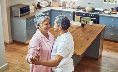 Buy stock photo Shot of a carefree elderly couple having a dance inside of the kitchen at home during the day