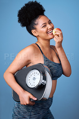 Buy stock photo Studio shot of a young woman holding an apple and her scale