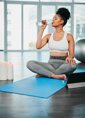 Buy stock photo Shot of a sporty young woman drinking water while doing yoga