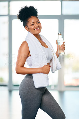 Buy stock photo Portrait of a fit young woman posing with a bottle of water