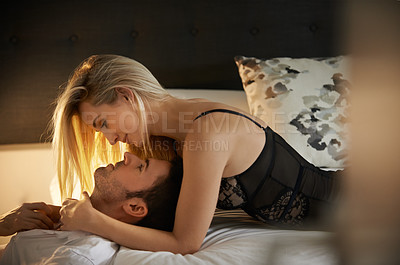 Buy stock photo Shot of a sexy young woman seducing her husband in the bedroom