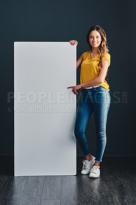 Buy stock photo Shot of a beautiful young woman standing next to a blank placard