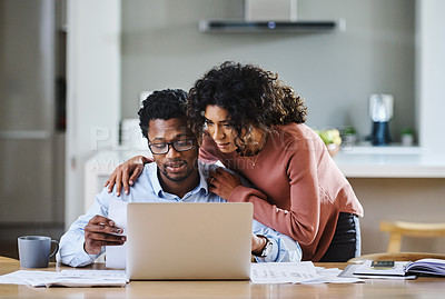 Buy stock photo Cropped shot of handsome young man using a laptop while his wife checks up on him at home