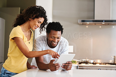 Buy stock photo Cropped shot of a young married couple using a tablet together in the kitchen at home